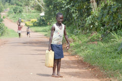African girl takes water home Stock Images