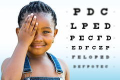 African girl testing vision. Close up Face shot of little African girl testing vision. Girl with braided hairstyle closing on eye with hand. Vision chart with stock photos