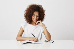 African girl thinking writing in notebook smiling over white background. Copy space. Beautiful african girl thinking writing in notebook smiling over white Stock Photo
