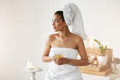 African girl with towel on head holding glass smiling looking in side resting in spa resort. Royalty Free Stock Photography