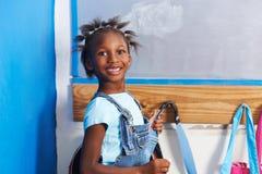 African girl at wardrobe of kindergarten Stock Photos