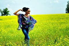 African girl wearing sunglasses stands on the field with flowers. African American girl wearing sunglasses, jeans and a tunic, stands with his hands on the field Royalty Free Stock Photo