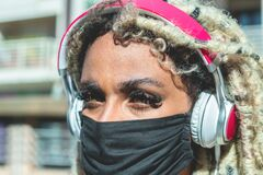 Free African Girl With Blond Dreadlocks Hair Listening Music While Wearing Face Protective Mask For Coronavirus Prevention - Covid 19 Royalty Free Stock Image - 191600976