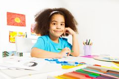 African girl writes letters sitting at table Stock Image