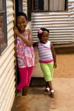 African girls. Two african girls standing at the door of their township shack. Poverty is very common in South African townships and all over Africa royalty free stock photography