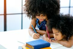 African girls as older and younger sister write or draw something on white paper near the book in front of glass windows with day. Light stock photo