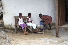 African girls sit in front of a house Stock Photo