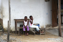 African girls sit in front of a house Stock Images