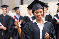 African graduate at ceremony. Pretty african american female graduate holding her diploma at ceremony Stock Image