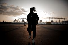 African guy with dreadlocks dancing on the background of sunset. Stylish afro-american man with dreadlocks and wearing black clothes and white sneakers dancing Stock Images