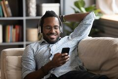 Free African Guy Holding Cellphone Listens Music Through Wireless Headphones Royalty Free Stock Image - 187755256