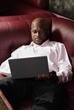 African guy with laptop on sofa Stock Photography
