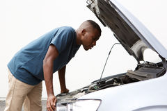 African guy looking under the hood of his broken down car. Side portrait of young african american guy looking under the hood of broken down car Stock Photo