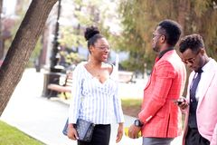 African guy is making the acquaintance of attractive positive girl oudoors stock image