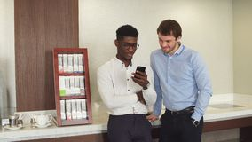 African guy with phone talking with his friend during the break. At work, rest time, free time stock video footage