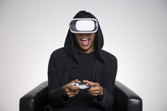 African guy playing vr game with controller. African American guy in a black hoodie is playing a virtual reality game. He is holding a controller and sitting in royalty free stock photography