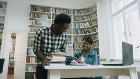 African guy walking to the library, giving five to attractive african girl and start studying together in the library. Handsome african guy in glasses walking stock video