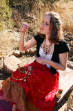 African gypsy 2. Woman sitting looking at jewellery Stock Images