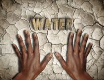 African hands on the ground arid and cracked Royalty Free Stock Images