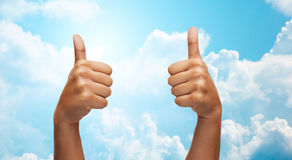 African hands showing thumbs up over blue sky Stock Photos
