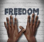 African hands on the wall with text Freedom Stock Image
