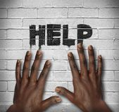 African hands on the wall with text Help Stock Photo