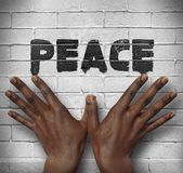 African hands on the wall with text Peace Royalty Free Stock Image