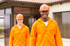 African handyman colleague. Smiling african handyman standing in front of colleague before house renovation royalty free stock photos