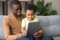 Black father teaching little son use tablet electronic device. African happy daddy holding son on lap sitting together on couch in room, loving father teach use royalty free stock images
