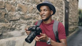 African happy tourist taking photo on his dslr camera. Young man travelling in Europe. African american happy tourist taking photo on his dslr camera. Young man stock photos