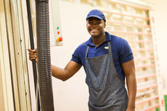 African hardware store worker. African male hardware store worker standing next to wood board cutting machine Stock Photography