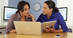 African and Hispanic businesswomen using laptop and tablet computer in office Stock Photos