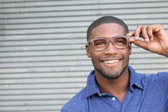 African holding his eyeglasses and smiling Stock Photos