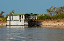 African Houseboat. Houseboat on the Zambesi River moored on the Namibia river bank Royalty Free Stock Photo
