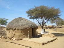 African hut. Cob cottage with thatched straw roof in African desert village, Africa Stock Photos