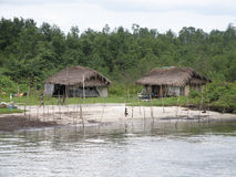 African hut in the tropics. The huts of local residents or aborigines along the river bank in Warri, Nigeria in tropical Africa Stock Photos