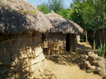 African Huts covered with trees. African tribal people house royalty free stock photography
