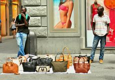 African immigrants in Italy. Selling fake bags and products to earn a living on the streets of Florence, Italy . they are often chased by the police for illegal Royalty Free Stock Photo