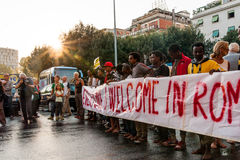 African immigrants march asking for hospitality for refugees Rome, Italy, 11 September 2015. Migrants holding banner at march in rome at sunset royalty free stock images