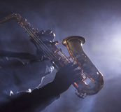African jazz musician playing the saxophone. In smokey club Stock Images