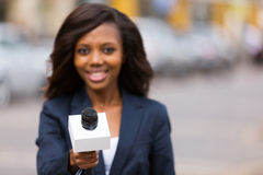 African journalist interviewing. Portrait of young african female journalist interviewing people on street Royalty Free Stock Photography