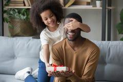 African kid daughter closing eyes congratulating dad giving gift box. Cute african kid daughter closing eyes congratulating black dad with happy birthday giving stock photos