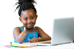 African kid doing thumbs up at desk isolated. Stock Photos