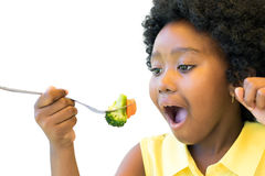 African kid eating vegetables. stock images
