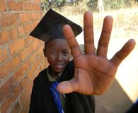 African kid in graduation attire showing open palm. Smiling African primary schoolkid wearing graduation attire showing an open palm or greeeting sign whilst royalty free stock photography