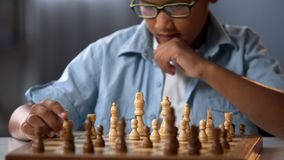 African kid moving knight piece during chess tournament, game strategy analysis stock images