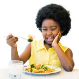 African kid pulling ugly face at dinner table. royalty free stock photos