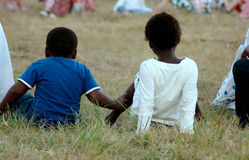 African kids. A group of African children sitting on the grass and watching a soccer game outdoors in South Africa stock image