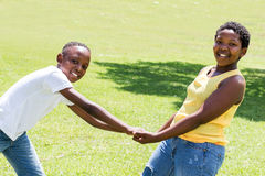 African kids holding hands in park. Medium shot of two african kids playing and holding hands against f¡green outdoor grass background royalty free stock images