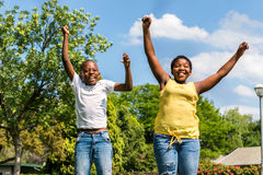 African kids jumping together in backyard. Close up action portrait of two african kids jumping together in outdoor park stock images